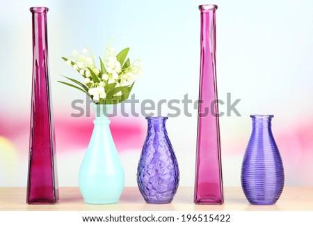 Different decorative vases on shelf on light background - stock photo