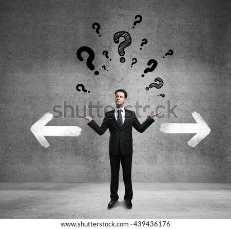 Different direction concept with confused businessman, question mark and arrow sketches in concrete room - stock photo