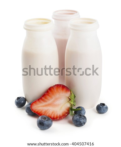 Different drinking yogurts in plastic bottles and berries on white background