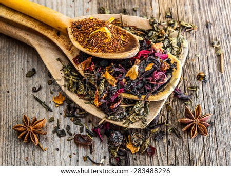 different dry teas in spoons on wooden background - stock photo