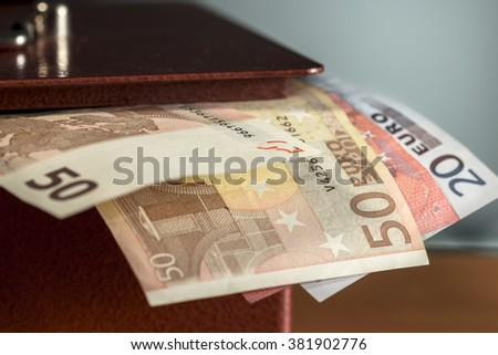 Different euro banknotes sticking out of a metal moneybox - stock photo