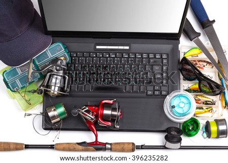 different fishing tackles on dark keyboard a black notebook. Concept design for freshwater outdoor active business company, on-line shopping, forums - stock photo