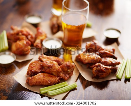 different flavored chicken wings on wax paper served with beer, ranch dressing and celery sticks - stock photo