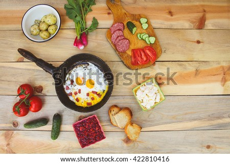 Different food: scrambled eggs in frying pan, boiled potatoes, curd, jam from viburnum, croutons, radishes, cucumbers, tomatoes, smoked sausage, croutons on wooden table. Toned image  - stock photo