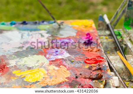 Different fresh blended oil paint on a bright milticolored artist's palette with professional paintbrushes - stock photo