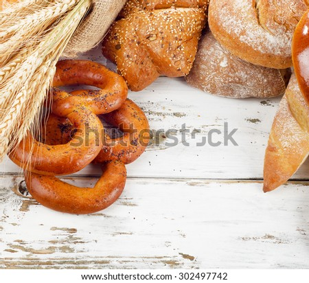 Different fresh bread and wheat on a white wooden table.