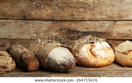 Different fresh bread, on old wooden table - stock photo
