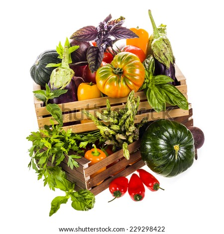 Different fresh vegetables and culinary herbs lie in colored wooden box isolated on white background - stock photo