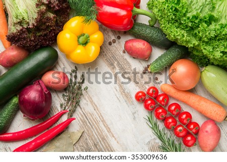 Different fresh vegetables separately on a wooden background cherry tomato pepper chilli peppers , potatoes, carrots , cucumber , rosemary , zucchini , onion , spices , lettuce - stock photo