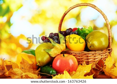 Different fruits and vegetables with yellow leaves in basket on table on bright background