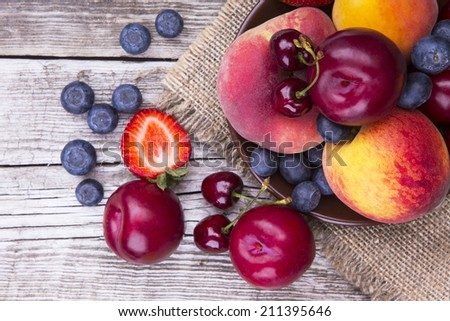 Different Fruits on Wood Textured Board - stock photo