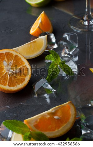 Different fruits with ice on the dark background