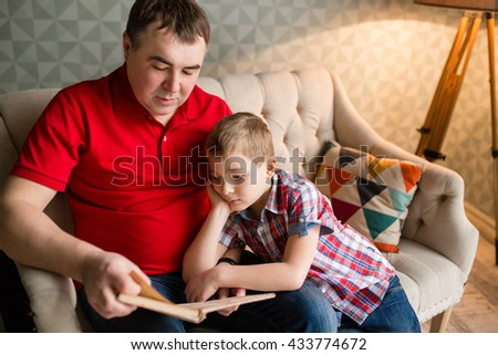 Different generations. Young father reading a book while his lovely son using a tablet device sitting at the home couch - stock photo