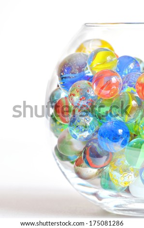 different glass balls in transparent bowl on white background - stock photo