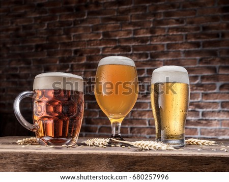 Different glasses of beer on the wooden table.