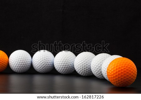 Different golf balls on the black table