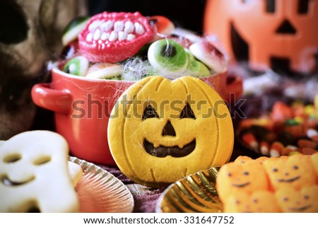 different Halloween candies and cookies on a table decorated with some scary ornaments, such as a skull, cobwebs or a carved pumpkin