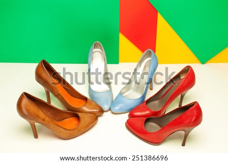 different high heels shoes on colored background - stock photo