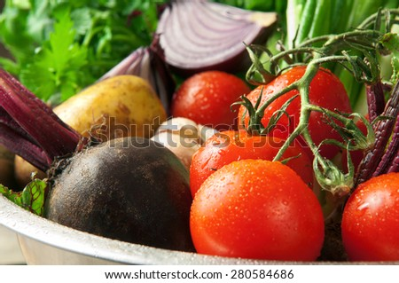 Different, home-grown fresh, young vegetables in an iron bowl, beets, green onions, bulb onion, cherry tomatoes, parsley, fennel, garlic, carrots lie on a wooden table. closeup. rustic style  - stock photo