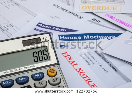 different invoices and bills and a calculator shows SOS, finacial concept - stock photo