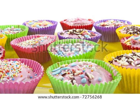 Different kind of decorated cup cakes on a glass  plate over white - stock photo