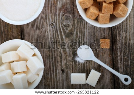 Different kind of white and brown sugar on old brown table . - stock photo