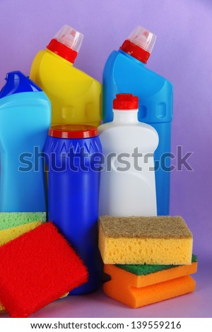 Different kinds of bath and toilet cleaners and colorful sponges, on color background