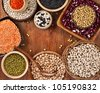 Different kinds of bean seeds, lentil, peas in dish on wooden table - stock photo