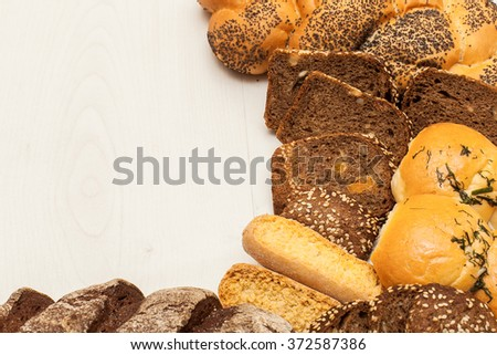 Different kinds of bread on a white table.