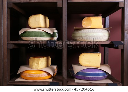 Different kinds of cheese on shelves in cellar - stock photo