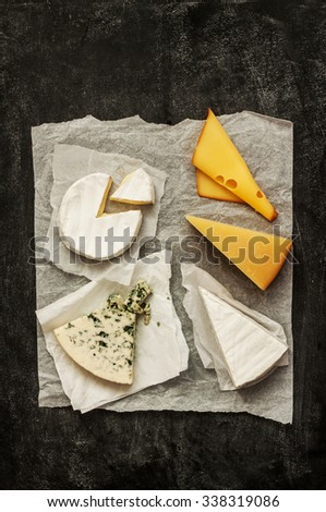 Different kinds of cheeses (camembert, brie, parmesan, blue cheese) captured from above (top view). Black chalkboard as background. Layout with free text space. - stock photo