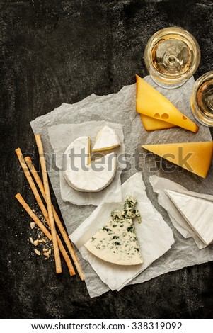 Different kinds of cheeses, white wine and snacks on black chalkboard background captured from above (top view). French tasting party or feast scenery. Poster layout with free text space. - stock photo
