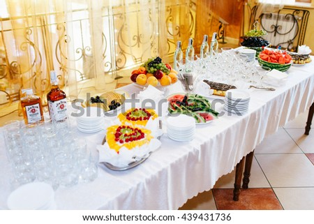 Different kinds of fruits and drinks lie on the table in white plates behind empty wineglasses - stock photo