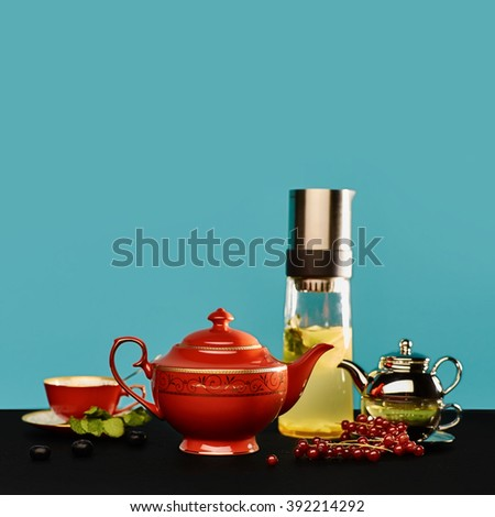 Different kinds of hot tea and tea ware. Red china teapot, red tea cup, glass thermos of ginger tea and little pot of green tea on a blue background. - stock photo