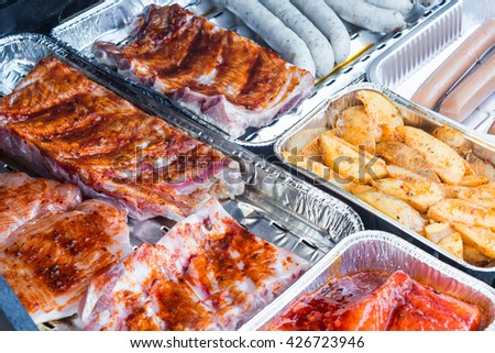 Different kinds of meat and grilled sausage on barbecue grill for great barbecue. - stock photo