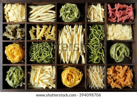 Different kinds of pasta in a wooden box. - stock photo
