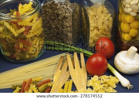 different kinds of pasta on the table, together with vegetables, ready for cooking - stock photo