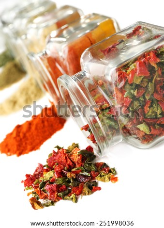 Different kinds of spices in glass bottles on white background - stock photo