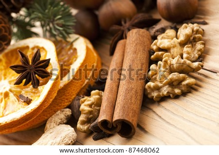 Different kinds of spices, nuts and dried oranges - christmas decoration - stock photo