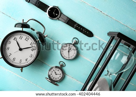Different kinds of watches on light-blue table. - stock photo