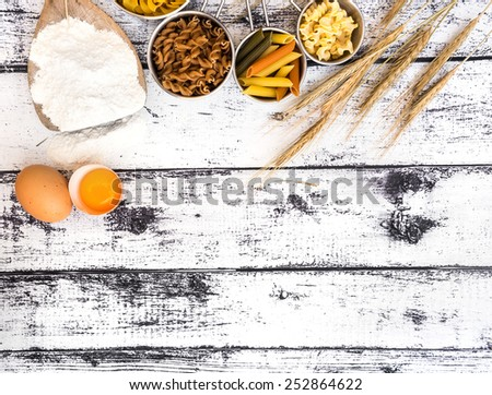 different kinds ofdifferent kinds of pasta on textured wooden table - stock photo