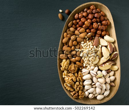 different knds of nuts in a wooden plate