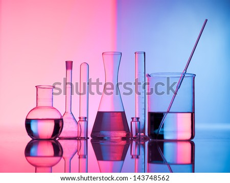Different laboratory glassware with water and empty with reflection. Pink and blue tint background - stock photo