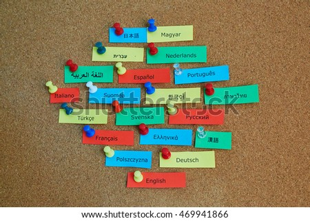 Different language names on colorful paper notes pinned to cork board