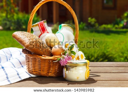 Different milk products: cheese, cream, milk, oil with bread, eggs and flowers. On a nature background