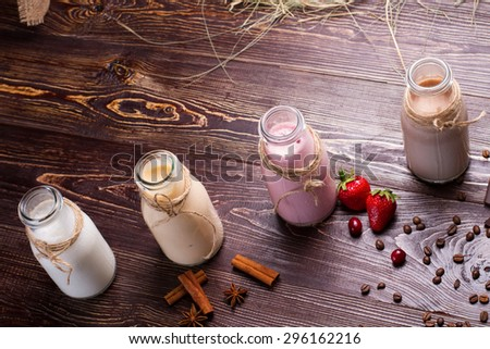 Different natural milkshakes on a wooden background. Ingredients for each cocktails. - stock photo