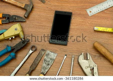 different old tools with smart phone on wood ,technology tools concept - stock photo