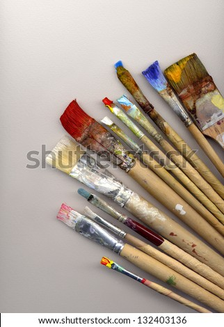 different paint brushes lying on white watercolor paper