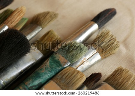 Different paintbrushes on fabric background - stock photo