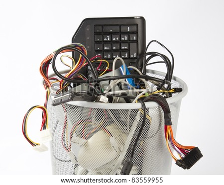 different parts of computers in trash can. Theren is a mouse, a keyboard, a power supply and many cables - stock photo